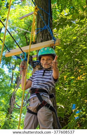 Brave little boy having fun at adventure park and giving  thumbs-up