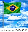 Brazil waving flag against blue sky - stock photo