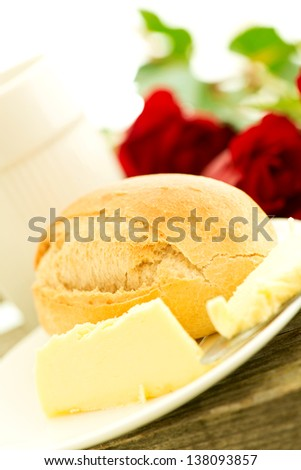 Bread butter and roses on wooden table - romantic breakfast  composition