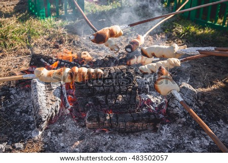 Bread on sticks over an outdoor campfire in the summer