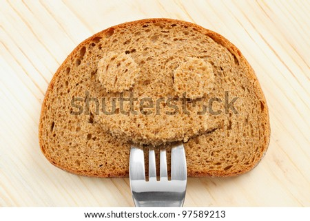Bread slice as smiling face with with a fork in your mouth