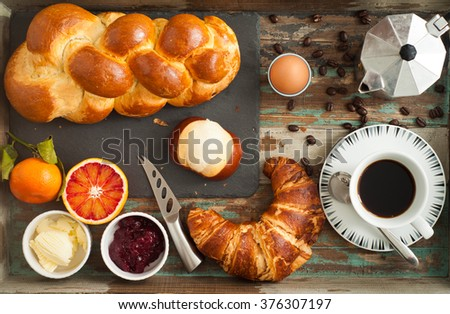 Breakfast flat lay of freshly baked bread, croissant, pretzel roll along with fruit, boiled egg and coffee. All served on a rustic wooden tray table.