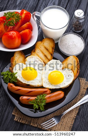 Breakfast on Valentine's Day - fried eggs in the shape of a heart and sausages, milk, tomatoes on the black wooden table.