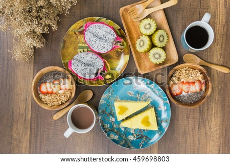 Breakfast set on  wooden table : Granola with strawberry and chia seed, dragon fruit, kiwi, pumpkin cake, hot coffee, hot chocolate flat lay