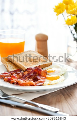 breakfast with bacon,fried egg,bread and orange juice