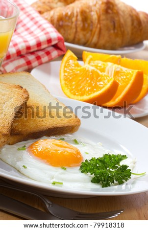 breakfast with  fried egg,  juice and croissant