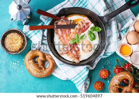Breakfast with fried eggs and bacon in cast-iron pan, broken egg, tomatoes, mustard, pretzels and basil on white kitchen towel over turquoise wooden background. Top view with copy space