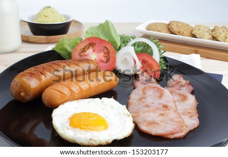 Breakfast with sausage, bacon, fried egg, orange juice, milk and ...