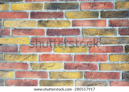 Brick wall background. Image of brick wall made of many different colors individual bricks yellow red grey