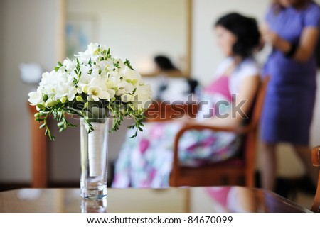Bridal bouquet and a bride getting ready on a background