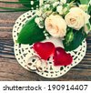 Bridal bouquet of white flowers on wooden surface. Wedding flowers, unusual designer florist bouquet of delicate roses. Wedding rings. Wedding bouquet, background. - stock photo
