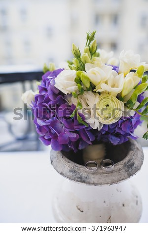 bridal bouquet of white roses and violets and herbs standing in the vase
