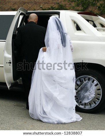bride and groom entering limousine