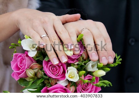 Bride and groom hands with engagement rings and wedding bouquet