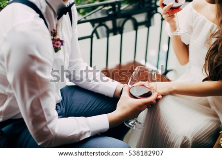 Bride and groom hold in their hands glasses with wine