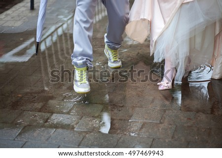 Bride and groom in stylish shoes stap over the pull on the road