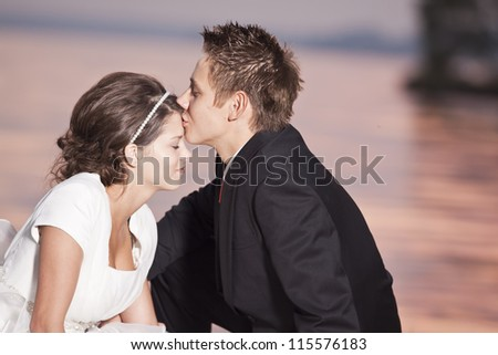 bride and groom, kissing at sunset on a beautiful beach