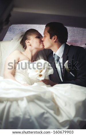 Bride and groom kissing. Happy young wedding couple in limo.