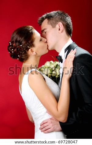 Bride and groom kissing on gray studio background