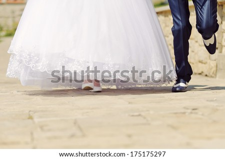 bride and groom running in sunny day