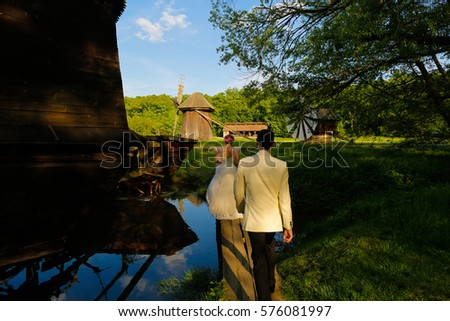 Bride and groom walking on a wooden bridge