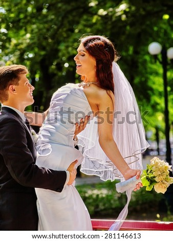 Bride and groom with flower summer  outdoor. Man holdig woman on hands.