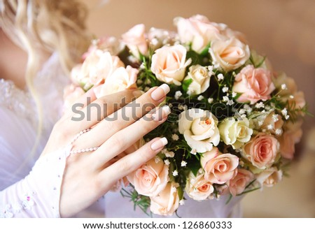 Bride hand with bridal bouquet of roses.