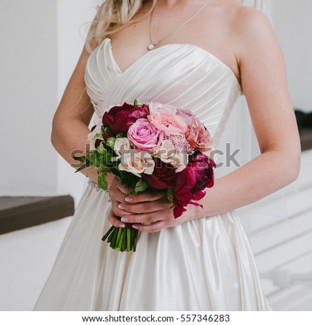 Bride holding wedding bouquet Burgundy color
