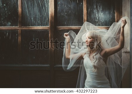 Bride holds her veil up posing behind an old big wooden window