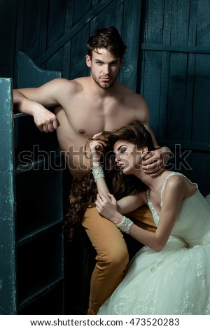 Bride in wedding dress and handsome young man with naked torso and muscular body posing in studio