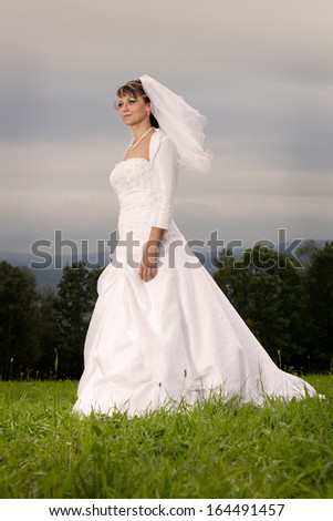 Bride in wedding dress on the green meadow