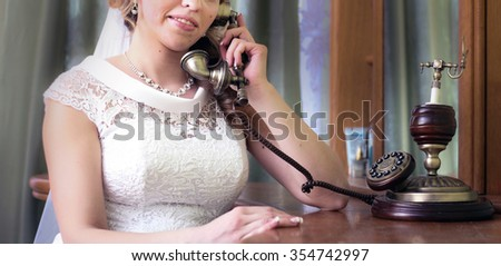 bride in white wedding dress sitting at Desk and talking on the phone
