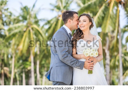 Bride is smiling with groom on the tropical beach