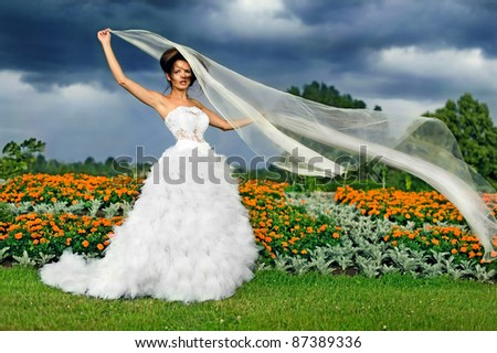 Bride on a background of black clouds and flower beds, keep the fabric in the wind