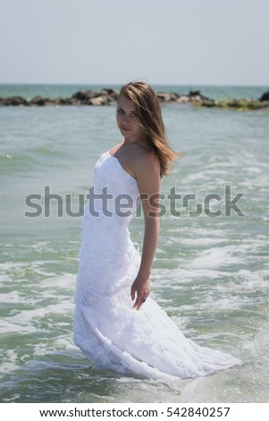 Bride running on the sea in a wedding dress. Bride of the sea in the summer. The waves and splashes. Happiness, mischief, new life