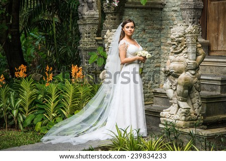 Bride with long veil in front of a Buddhist structure