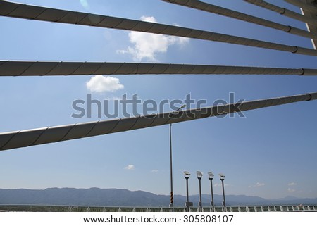 Bridge cables against the blue sky with street lamps, mountains, and white clouds in the background