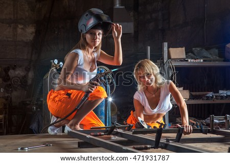 Brigade of two sexy welder women on the workshop background.
