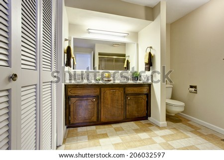 Bright bathroom interior with dark brown vanity cabinet with mirror