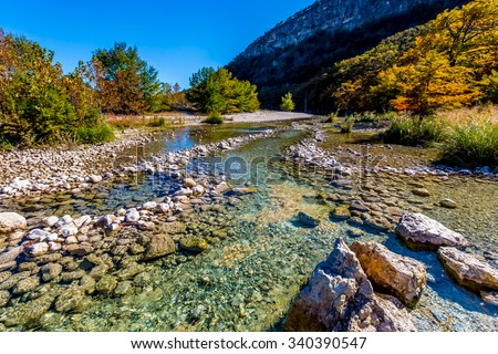 Bright Beautiful Fall Foliage on the Banks of the Rocky Crystal Clear Frio River.