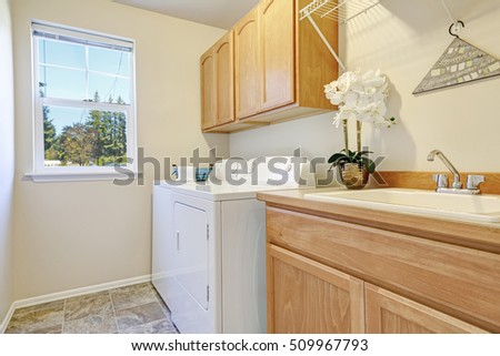 Bright interior of laundry room with cabinets and white appliances. Northwest, USA