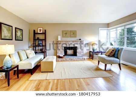 Bright Living Room With A Hardwood Floor And Rocky Background Fireplace.  Furnished With Classic Sofa