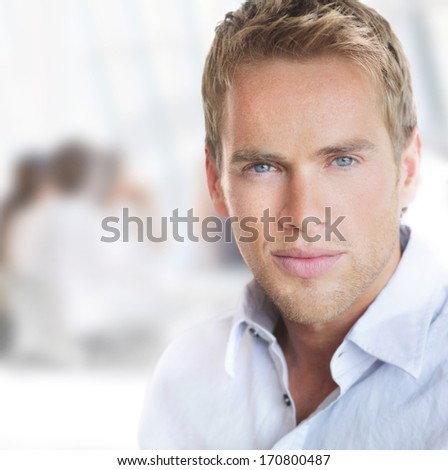 Bright portrait of a young good-looking successful businessman in office setting