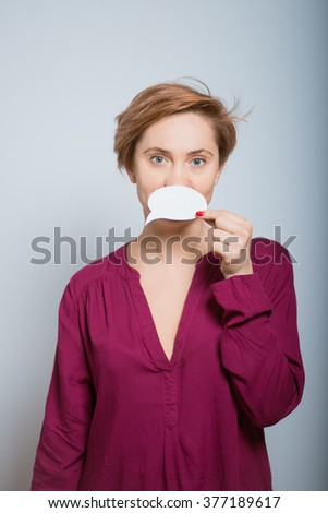 Bright woman holding a white sticker, studio isolated