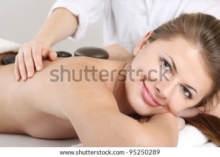 Bright young woman enjoying a back massage with hot stone in a spa