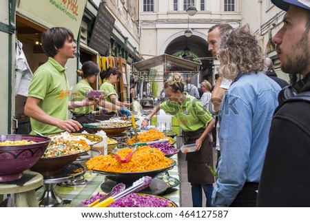 Bristol, United Kingdom - 2 August 2016: Landscape image of street food vendors serving customers healthy snacks and meals in St Nicholas Market in Bristol, UK