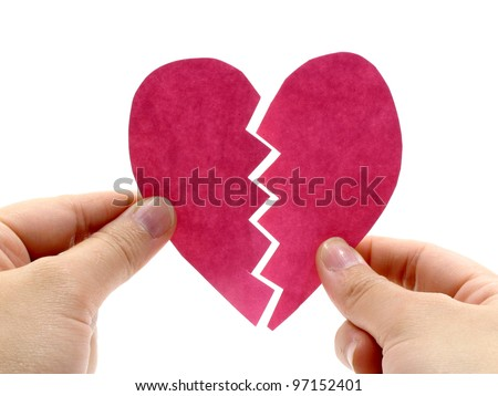 Broken pink heart is holding by hand on white background
