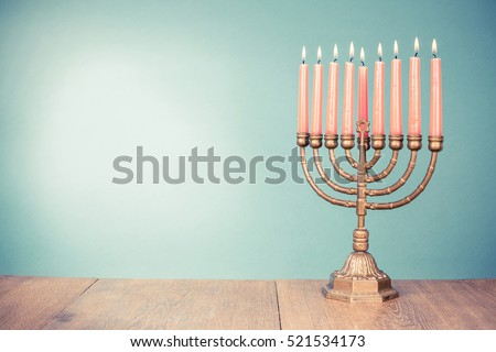 Bronze Hanukkah menorah with burning candles for holiday card background. Retro old style filtered photo