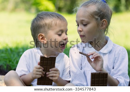 Brother and sister having fun eating chocolate outdoors. Summer day in park.