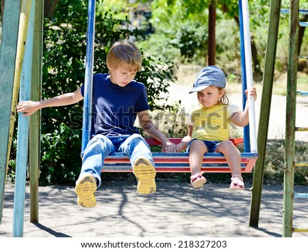 brother and sister on the swing in the park
